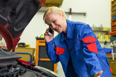 Woman as a mechanic in car workshop Royalty Free Stock Photos