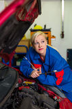 Woman as a mechanic in car workshop Stock Images