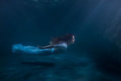 Woman as the mermaid under water. Woman as the mermaid swims under water, she in a white dress Royalty Free Stock Photos