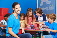 Woman as nursery teacher in kindergarten. With group of children painting at table Stock Photography