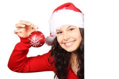 Woman as santa with red christmas bauble. Young woman as santa with red christmas bauble behind white board Royalty Free Stock Image
