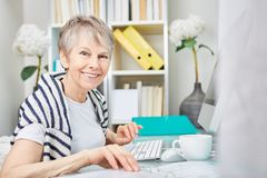 Woman as senior business citizen. Working at her place of work stock photography