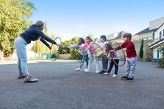 Sports teacher shows kids exercise with tires royalty free stock images