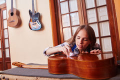 Woman as trainee cleaning guitar Stock Photo