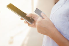 Woman asian using phone and credit card shopping online , select. Ive focus on hand Stock Photography