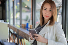 woman asian using phone for shopping online and calling with cell telephone in coffee shop during free time royalty free stock photography