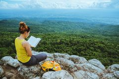 Woman asians travel relax in the holiday. Sitting. Read a book. View mountain nature on the cliffs. Travel nature. Travel relax royalty free stock photography