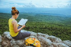 Woman asians travel relax in the holiday. Sitting. Read a book. View mountain nature on the cliffs. Travel nature. Travel relax stock images