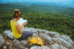 Woman asians travel relax in the holiday. Sitting. Read a book. View mountain nature on the cliffs. nEducation, reading royalty free stock photography