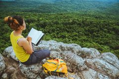 Woman asians travel relax in the holiday. Sitting. Read a book. View mountain nature on the cliffs. Education, reading royalty free stock photography