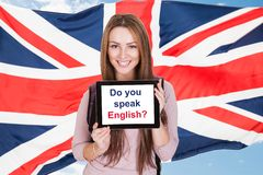 Woman Asking Do You Speak English. Young Woman Holding Digital Tablet Asking Do You Speak English In Front Of British Flag Royalty Free Stock Photos