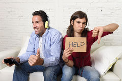 Woman asking for help angry upset while husband or boyfriend plays videogames ignoring her Stock Photos