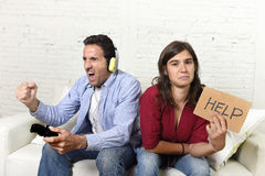 Woman asking for help angry upset while husband or boyfriend plays videogames ignoring her. Young attractive women asking for help angry and upset while husband Royalty Free Stock Images
