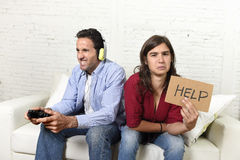 Woman asking for help angry upset while husband or boyfriend plays videogames ignoring her Stock Image