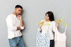 Woman asking her boyfriend about dresses. Young women asking her boyfriend about choosing dresses isolated royalty free stock image