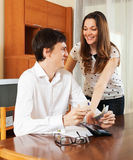 Woman asking husband for money at home stock photography