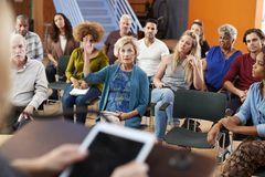 Free Woman Asking Question At Group Neighborhood Meeting In Community Center Royalty Free Stock Image - 153623546