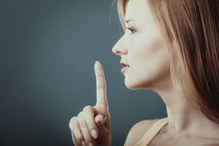 Woman asking for silence finger on lips royalty free stock photo
