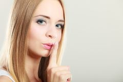 Woman asking for silence finger on lips stock photos