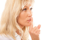 Woman asking for silence finger on lips hush gesture. Woman asking for silence or secrecy with finger on lips hush hand gesture. Isolated Stock Images