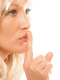 Woman asking for silence finger on lips hush gesture. Woman asking for silence or secrecy with finger on lips hush hand gesture. Isolated Stock Photo