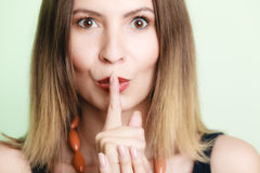 Woman asking for silence with finger on lips Royalty Free Stock Photos