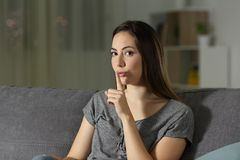Woman asking for silence in the night at home. Woman asking for silence with finger on lips in the night sitting on a couch in the living room at home Stock Images