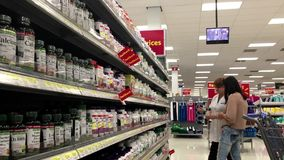 Woman asking worker about health food question at pharmacy section stock footage