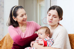 Woman asks for forgiveness from adult daughter with baby. Mature women asks for forgiveness from adult daughter with baby after quarrel royalty free stock photo