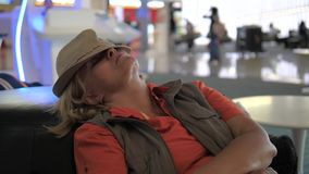 A woman asleep in the airport chairs waiting for a delayed plane departure. A tourist woman sleeps at the airport on the couch, waiting for the departure of the stock footage