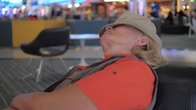 A woman asleep in the airport chairs waiting for a delayed plane departure. A tourist woman sleeps at the airport on the sofa in the recreation area, awaits the stock video