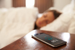 Woman Asleep In Bed Woken By Alarm On Mobile Phone Royalty Free Stock Photography