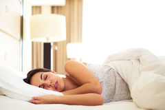 Woman asleep on her side in bed Stock Photos