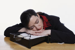 Woman Asleep on Inbox. Businesswoman asleep on her inbox. Isolated against a white background stock photo