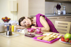 Woman asleep on kitchen table during breakfast Royalty Free Stock Photography