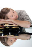 Woman asleep over her guitar Stock Photos