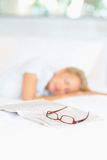 Woman asleep after reading newspaper in bed Royalty Free Stock Image