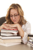 Woman asleep on stack of books. A woman sleeping on top of her books with her eyes closed Royalty Free Stock Photo