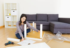 Woman assemble furniture. At home stock images