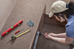 Woman assembles furniture, hinges lifting mechanism screwed to b Stock Photo