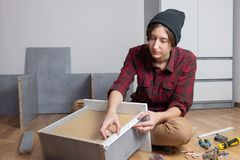 Woman assembling a chest drawer for new bedroom furniture. royalty free stock image