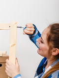 Woman assembling wood furniture using hex key. DIY Royalty Free Stock Photography