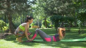 Woman with assistance of female friend doing sit-ups. Charming sporty woman with ponytails exercising sit-ups with assistance of female friend in summer park stock footage
