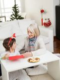 Woman Assisting Boy In Making Christmas Greeting Royalty Free Stock Photography
