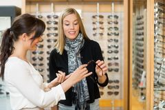 Woman Assisting Customer In Selecting Glasses Royalty Free Stock Image
