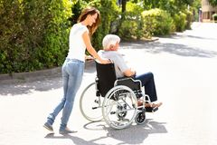 Woman Assisting Her Disabled Father On Wheelchair stock image