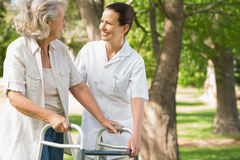 Woman assisting mature female with walker at park Stock Photos