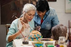 Woman assisting senior woman in painting bowl at drawing class. Attentive women assisting senior women in painting bowl at drawing class Royalty Free Stock Image