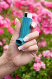 And of woman with asthma aerosol. Closeup of hand of woman with asthma aerosol in outdoor near pink flowers Stock Image