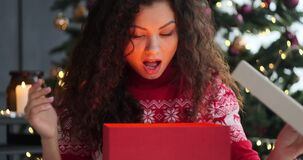 Excited woman opening surprise Christmas gift